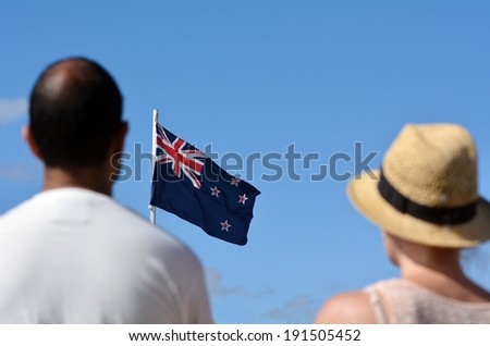 MANGONUI, NEW ZEALAND - APRIL 25 2014: New Zealander couple stands under New Zealand flag during the National War Memorial service. - stock photo