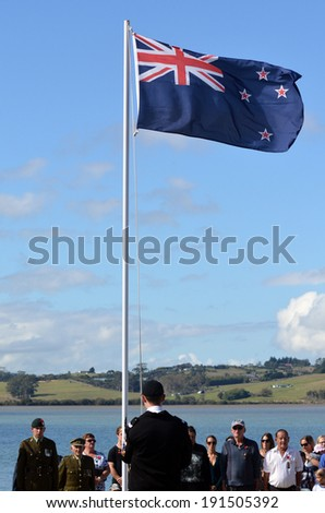 MANGONUI, NEW ZEALAND - APRIL 25 2014: Young New Zealander man is lowering the flag of New Zealand during the National War Memorial day. - stock photo