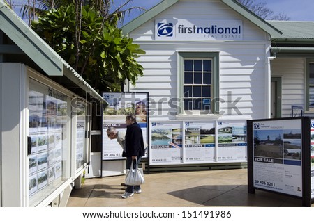 MANGONUI,NZ - AUG 24:Couple looks at house listing on a signpost of Real Estate office on Aug 24 2013.NZ house prices are booming with the average price of an Auckland city home rocketing to $735,692.