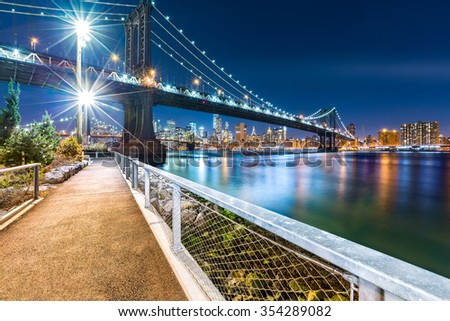 Manhattan Bridge by night, viewed from John Street Park with Brooklyn Bridge and Lower Manhattan skyline in the background. - stock photo