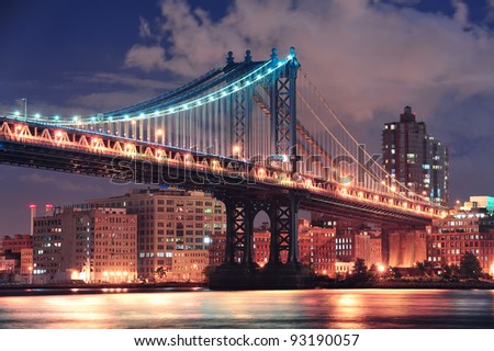 Manhattan Bridge closeup over East River at night in New York City Manhattan with lights and reflections.