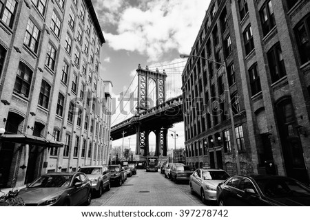 Manhattan bridge seen from a brick buildings in Brooklyn street in perspective, New York, USA. Business and travel background. Vintage, retro postcard. - stock photo