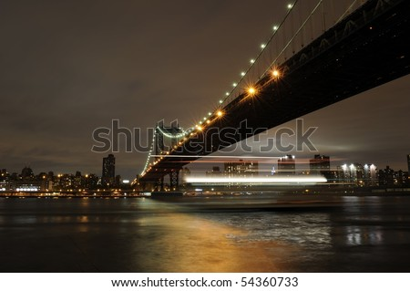 Manhattan Bridge with a cruise boat passing underneath. - stock photo