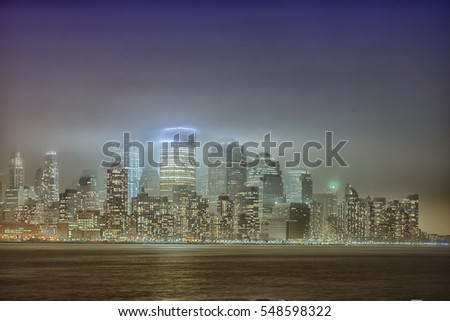 Manhattan cityscape at night in fog. Special foggy effect. Monochrome colors.