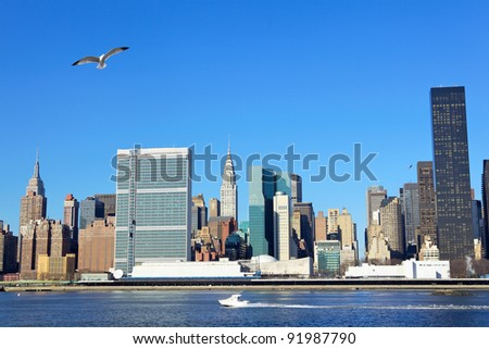Manhattan midtown skyline over East River with urban skyscrapers and blue sky - stock photo