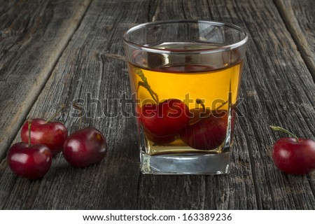 Manhattan or other whiskey cocktail, with cherries submerged and cherries next to it - stock photo