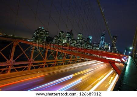 Manhattan skyline and cars crossing Brooklyn Bridge at night, New York City - stock photo