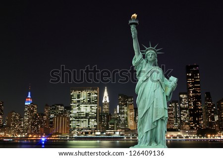 Manhattan Skyline and The Statue of Liberty at Night, New York City - stock photo