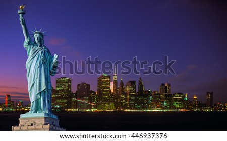 Manhattan skyline at night with blue sky and illuminated buildings and Statue of Liberty.