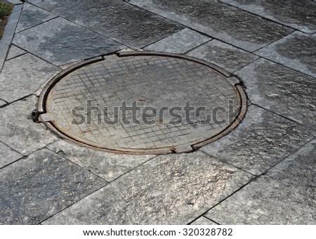 Manhole cover on garden pavement - stock photo