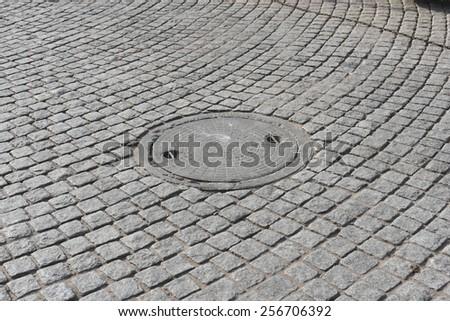 Manhole cover on pavement in Gurgaon, India - stock photo