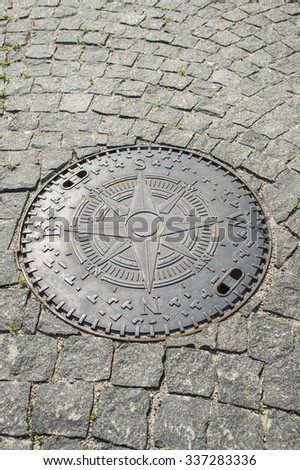 manhole with wind rose on the stone pavement - stock photo