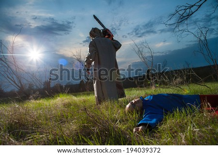 Maniac with the chainsaw dressed in a dirty bloody raincoat. Victim on the foreground, sunset forest on the background. - stock photo