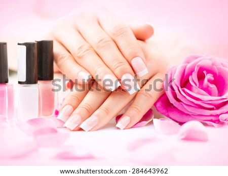 Manicure and Hands Spa. Beautiful Woman hands closeup. Manicured nails and Soft skin. Beauty hands with rose flower petals. Beauty treatment. Beautiful woman's nails with beautiful french manicure  - stock photo