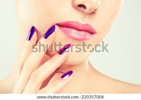 Manicure and Makeup  ?beautiful purple nails and soft lips - stock photo