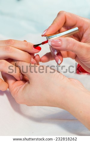 Manicure. applying red nail polish. Closeup of Woman applying nail varnish to finger nails.Manicure process.Beautiful manicure process. Nail polish being applied to hand, polish in red color - stock photo