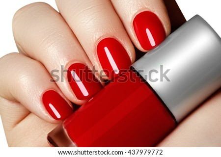 Manicure. Beautiful manicured woman's hands with red nail polish. Bottle of nail polish.Trendy red nails