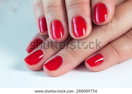 Manicure - Beautiful manicured woman's hands with red nail polish on soft white towel