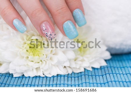 Manicure - Beautifully manicured woman's hand with interesting nail art touching flower. Close-up. Selective focus. - stock photo