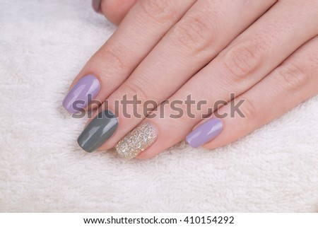 Manicure - Beauty photo of nice manicured woman fingernails. Very nice feminine nail art with nice purple,silver and grayish nail polish. - stock photo