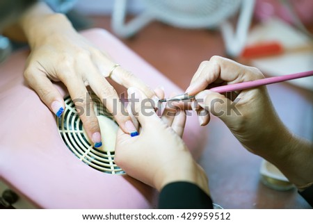 Manicure. Beauty saloon. Close-up.Apply  nail and blur tone - stock photo