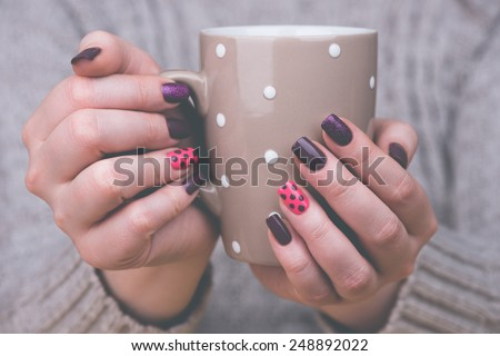 Manicure - Beauty treatment photo of nice manicured woman fingernails. Very nice feminine nail art with nice pink and purple nail polish. Processed in retro colors. Selective focus. - stock photo