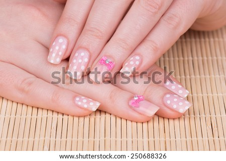 Manicure - Beauty treatment photo of nice manicured woman fingernails. Very nice feminine nail art with polka dots and bow detail. Selective focus. - stock photo
