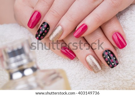 Manicure - Beauty treatment photo of nice manicured woman fingernails. Very nice feminine nail art with nice pink, gold and black nail polish. - stock photo