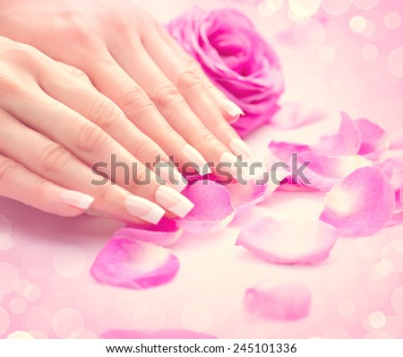 Manicure, Hands spa Beautiful feamle hands, soft skin, beautiful nails with pink rose flowers petals. Healthy Woman hands. Beauty salon. Beauty treatment. Beautiful nails with french manicure  - stock photo