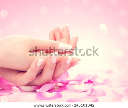 Manicure, Hands spa Beautiful feamle hands, soft skin, beautiful nails with pink rose flowers petals. Healthy Woman hands. Beauty salon. Beauty treatment. Beautiful nails with french manicure