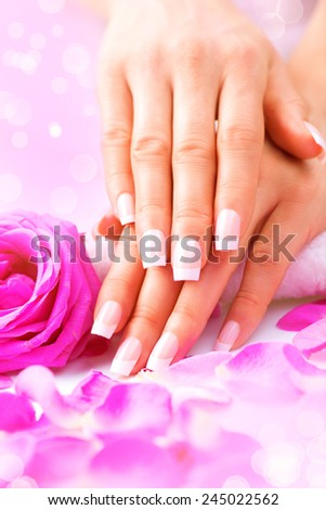 Manicure, Hands spa. Beautiful female hands, soft skin, beautiful nails with pink rose flowers petals. Healthy Woman hands. Beauty salon. Treatment. Beautiful woman's nails with french manicure  - stock photo