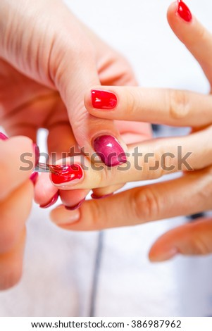 Manicure in progress - Beautiful manicured woman's nails with red nail polish. The industry of beauty and nail care, beauty salons, soft focus