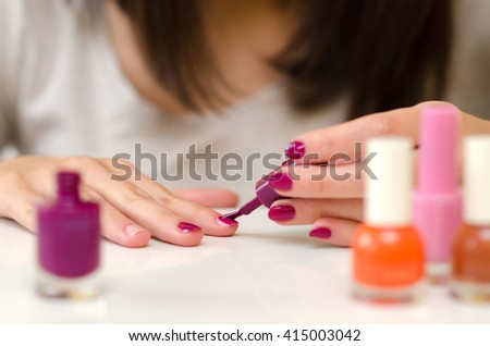 Manicure nail paint purple color on white table at home.