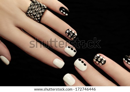Manicure on short nails covered with black and white lacquered with rhinestones on a black background. - stock photo