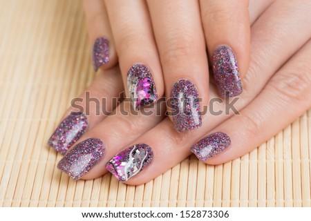 Manicure - Professionally manicured woman fingernails, with interesting nail art. Studio shot. Selective focus.  - stock photo