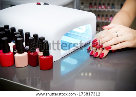Manicure set in a beauty salon. Beautiful female hands. - stock photo