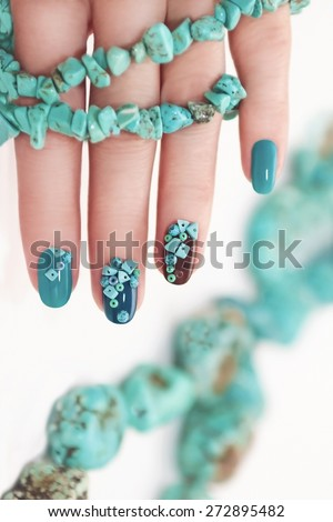 Manicure with beads and turquoise in the form of small stones and jewelry made of turquoise on the woman's hand. - stock photo