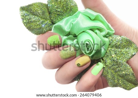 Manicure with green rose and a different design of sequins and rhinestones on nails. - stock photo