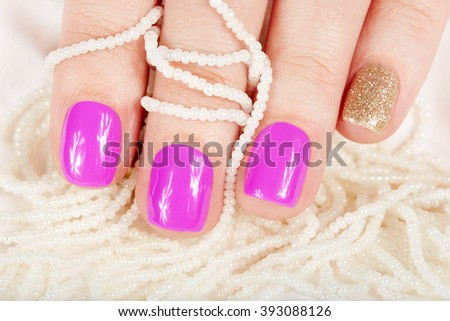 Manicured nails covered with pink nail polish and pearl necklaces - stock photo