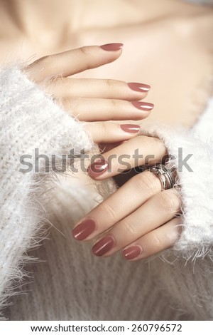 Manicured woman fingernails with natural color nail polish. Manicure and beauty treatment. Warm, soft white sweater and shiny gold rings with brilliants on fingers. Selective focus.  - stock photo