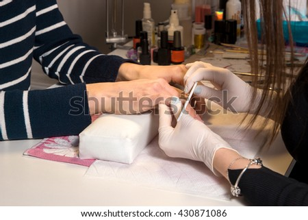 Manicurist files the nails - stock photo