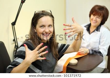 manicurist made manicure for woman in beauty salon; happy customer shows her nails; focus on client - stock photo