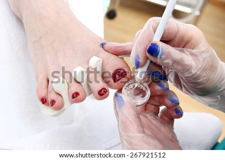 Manicurist treating client at beauty salon. Manicure stage: gluing crystals on nail - stock photo