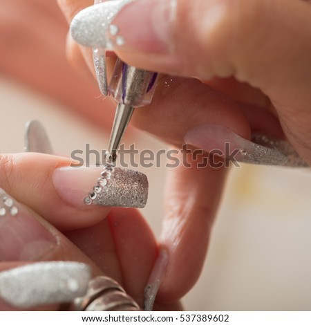 Manicurist treating customer at beauty salon - doing artifical nails