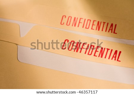 Manila folder with confidential stamps in red. - stock photo