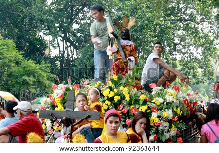 MANILA - JAN. 9: Devotees celebrate the feast of The Black Nazarene on January 9, 2012 in Manila Philippines. Image of the Black Nazarene parade around the city attended by thousands of devotees.. - stock photo
