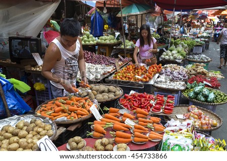 Manila, Philippines - July 16, 2016: Seller and customer in a street market