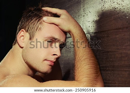 Manly and muscular. Closeup rear view image of sexual man leaning with his hands against the tile wall and looking away with water drops on his skin