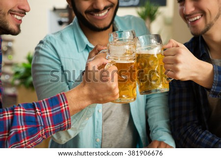 Manly leisure. Cropped shot of cheerful male friends enjoying beer at the local pub cheering with their drinks - stock photo