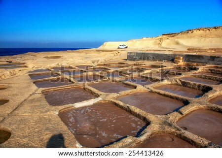 Manmade salt pools on a Gozo coastline - stock photo